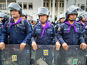 04 DECEMBER 2013 - BANGKOK, THAILAND:  Women Thai police stand in formation in front of riot police during an antigovernment protest at police headquarters in Bangkok. Several hundred anti-government protestors tried to occupy Royal Thai Police Headquarters on Rama I Road in central Bangkok Wednesday. The protest was one of the continuing protests against the government of Prime Minister Yingluck Shinawatra. Police commanders allowed protestors to tear down police barricades and ordered riot police to lay down their shields. Protestors then chanted anti-government slogans and called on police to turn against the government before forming a motorcade and leaving the area. Anti-government protests have gripped Bangkok for nearly a month and protestors vow to continue their actions. Protests Wednesday were much smaller and more peaceful than protests earlier in the week.     PHOTO BY JACK KURTZ