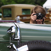 A young member of the judging team takes photographs of a 1928 Stutz BB at the Greenwich Concours d'Elegance Festival of Speed and Style featuring great classic vintage cars. Roger Sherman Baldwin Park, Greenwich, Connecticut, USA.  2nd June 2012. Photo Tim Clayton