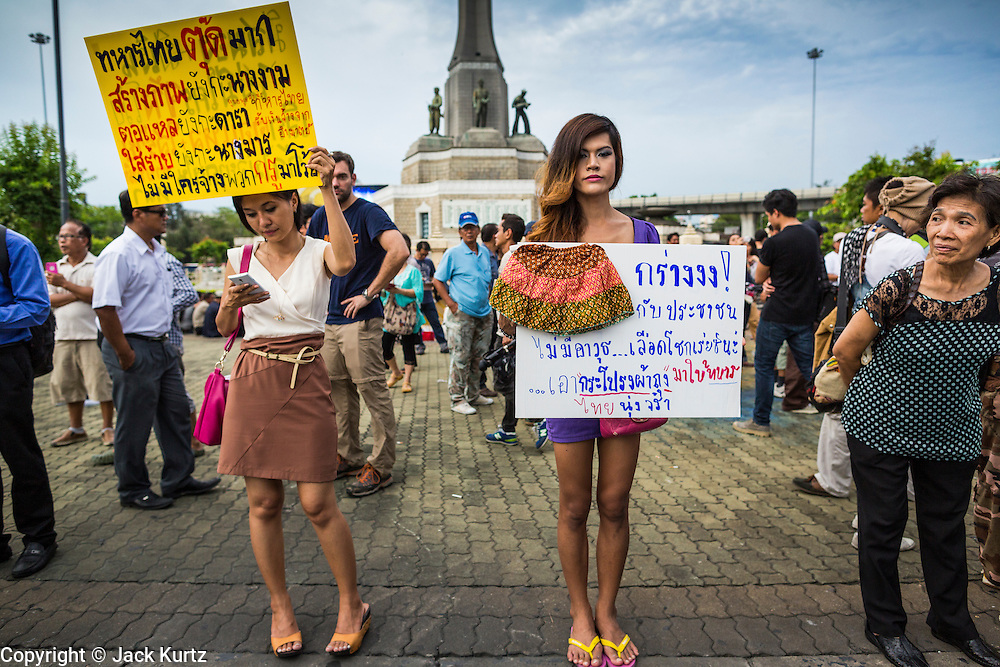"27 MAY 2014 - BANGKOK, THAILAND: Two women and a ""katoey"" or ladyboy, at Victory Monument in Bangkok protest against the coup. Several hundred people protested against the coup in Bangkok at Victory Monument. It was the fourth straight day of pro-democracy rallies in the Thai capital as the army continued to tighten its grip on Thai life. The protest Tuesday was the smallest so far.     PHOTO BY JACK KURTZ"