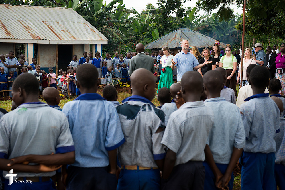 The Rev. Dr. John Juedes, pastor of Messiah Lutheran Church in Highland, Calif., addresses an assembly of approximately five hundred school children after arriving Monday, June 9, 2014, at the Luanda Doho Primary School in Kakmega County, Kenya. Juedes is part of a 14-member Mercy Medical Team using a part of the school for a week-long medical clinic. LCMS Communications/Erik M. Lunsford