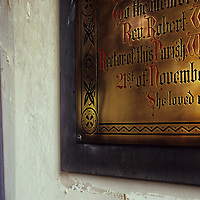 Corner of Victorian brass memorial plaque in warm light next to cream wall and purple curtain