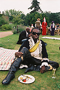 Man in historical fancy dress costume eating in the garden, Posh at Addington Palace, UK, August, 2004
