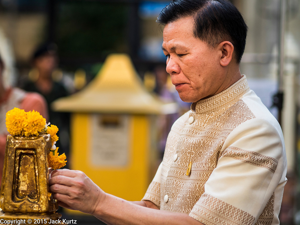 03 SEPTEMBER 2015 - BANGKOK, THAILAND:     KRITSAYAPONG SIRI, Director-General of the Religious Affairs Department of the Thai Ministry of Culture, makes merit by applying gold leaf to Erawan Shrine in Bangkok Thursday. Repairs to Erawan Shrine were completed Thursday, Sept 3 after the shrine was bombed on August 17. Twenty people were killed in the bombing and more than 100 injured. The statue of the Four Faced Brahma in the shrine was damaged by shrapnel and a building at the shrine was damaged by debris.   PHOTO BY JACK KURTZ