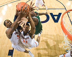 Virginia forward Mike Scott (32) and Virginia forward/center Jerome Meyinsse (55) grab a rebound against USF.  The Virginia Cavaliers defeated the South Florida Bulls 77-75 at the University of Virginia's John Paul Jones Arena in Charlottesville, VA on November 19, 2008.