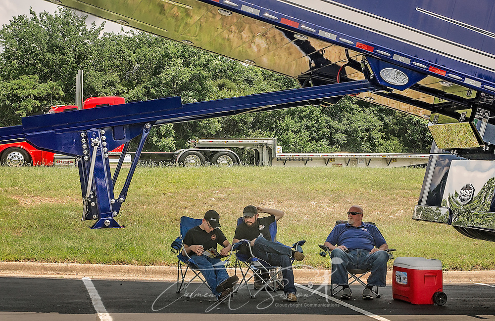 Jacob Leister, Luke Leister, and Rich Hart, keep cool beneath their truck, a 2015 Peterbilt 389 with a 2017 MAC End Dump, during the 34th annual Shell Rotella SuperRigs truck beauty contest, June 11, 2016, in Joplin, Missouri. They were awarded Best Lights. SuperRigs, organized by Shell Oil Company, is an annual beauty contest for working trucks. Approximately 89 trucks entered this year's competition. (Photo by Carmen K. Sisson/Cloudybright)