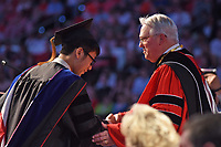 Chancellor Randy Woodson (right) congratulates a newly conferred doctor.