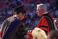 Chancellor Randy Woodson (right) congratulates a newly conferred doctor.