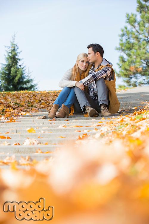 Full length of couple sitting on steps in park
