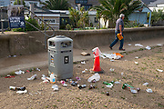 The morning after Saturday night crowds of young peoples' nightlife beach parties, their litter and rubbish from the night before stretches across the coastal paths and shingle, a man walks along a messsy sea wall, on 19th July 2020, in Whitstable, Kent, England.  A group of local volunteers and council cleaner will soon arrive for the regular morning clean-up that has got worse, they say, during the Coronavirus pandemic lockdown and now, the slow easing of health guidelines.