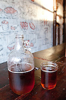 A growler of beer with a mason jar glass on a table at Fette Sau, Brooklyn, NYC