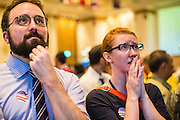 07 NOVEMBER 2012 - BANGKOK, THAILAND:  COLIN CHENEY, left, and MARY CONGER watch as US election results are posted at the US Embassy's election watch party in Bangkok. They both supported President Obama's reelection. US President Barack Obama won a second term Tuesday when he defeated Republican Mitt Romney. Preliminary tallies gave the President more than 300 electoral votes, well over the 270 needed to win. The election in the United States was closely watched in Thailand, which historically has very close ties with the United States. The American Embassy in Bangkok sponsored an election watching event which drew thousands to a downtown Bangkok hotel. American Democrats in Bangkok had their own election watch party at a restaurant in Bangkok.      PHOTO BY JACK KURTZ