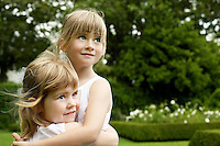 Two young girls in garden hugging looking away