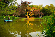 Old Westbury, New York, U.S. 22nd June 2013. Visitors stroll by the pond at dusk, at the Midsummer Night event at Old Westbury Gardens, on the grounds of the historic Long Island Gold Coast estate.