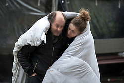 © Licensed to London News Pictures . 06/04/2017 . Manchester , UK . A man and a woman stagger along Piccadilly Gardens , wrapped in a duvet . An epidemic of abuse of the drug spice by some of Manchester's homeless population , in plain sight , is causing users to experience psychosis and a zombie-like state and is daily being witnessed in the Piccadilly Gardens area of Manchester , drawing large resource from paramedic services in the city centre . Photo credit : Joel Goodman/LNP