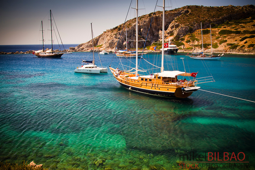 Bay and sailing ships near Knidos ancient Greek city ruins.<br /> Datca peninsula, Mugla province, Turkey.