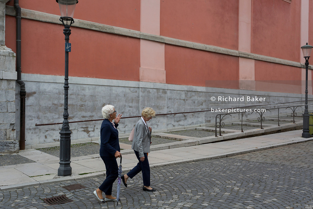 Two ladies walk up Miklosiceva Cesta (street) in the Slovenian capital, Ljubljana, on 28th June 2018, in Ljubljana, Slovenia.