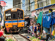27 SEPTEMBER 2016 - BANGKOK, THAILAND:  The State Railways of Thailand train comes into the station in Samut Songkhram. The train from Baen Laem to Samut Songkhram (Mae Khlong) recently resumed service. The 33 kilometer track was closed for repair for almost a year. In Samut Songkhram, the train passes over the market. Vendors pull their stands out of the way and people step out of the way as the train passes through the market. It is one of the most famous train stations in Thailand and has become an important tourist attraction in the community.    PHOTO BY JACK KURTZ