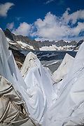 Huge sheets with fleece blankets cover an ice tunnel at the mouth of the Rhone Glacier in Switzerland. After a winter with record amounts of snow, most of it was gone when this imae was taken on July 14th 2018, exposing the darker ice. While snow is a brilliant reflector of the energy from the sun, the darker ice absorbs the energy instead, accelerating the melting of the glacier. The color and darkness of glacier ice vary all over the world, depending on build-up of pollution, age of the ice, particles picked up by the ice and by microorganisms in the ice. The glacier ice is however rarely white as snow. With shorter winters and vanishing snow cover, the melting of the glaciers is accelerating.<br /> The Rhone Glacier now melts more than 70 centimeters in thickness every week during the summer months. Between 1996 and 2006, an estimated 0.9 billion cubic metres of water melted yearly from the Swiss glaciers. That number is likely much higher today. Switzerland just had the hottest July since 1921, and the rivers are running at record low levels.<br /> The ice tunnel is a popular tourist attraction, and has been a steady income source for the Carlen family who runs and maintain the ice tunnel. The fleece blankets help slow down the melting. While tourists always have flocked to the Rhone Glacier due to it's easy access from the nearby Furka Pass, today's tourism is often visitors who are concerned about the effects of climate change.