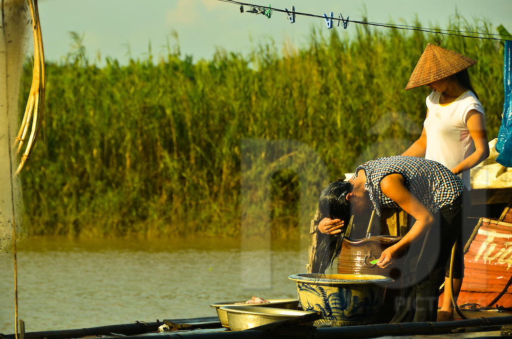 Woman washing their hair on one of the boat of people living on the banks of the Red River in Hanoi.
