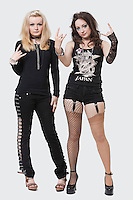 Full length portrait of two young female punks gesturing rock & roll hand sign over white background