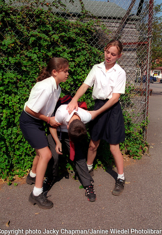 Girls bullying smaller boy at school modelled.