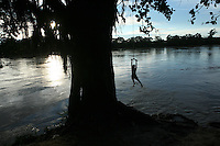 A boy plays at a swimming hole along the Arauca River, which borders Colombia and Venezuela, just outside of the Colombian city of Arauca on June 27, 2009. The border region between Colombia and Venezuela has often been a region with a high level of activity of illegal armed groups. (Photo/Scott Dalton)