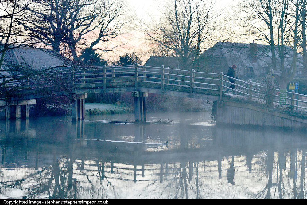 © Licensed to London News Pictures. 29/12/2013. East Bergholt, UK. A woman walks across a bridge at Flatford Mill.  Early morning frost and mist on the River Stour at Deadham Vale this morning 29th December 2013. Photo credit : Stephen Simpson/LNP