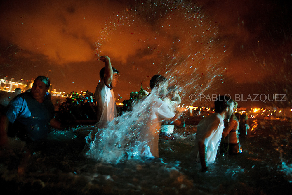 15/08/2016. Fishermen and worshippers splash water after take the image of the Virgin of Palm back to the sea during the yearly Virgin of Palm maritime pilgrimage at El Rinconcillo beach on August 15, 2016 in Algeciras, Spain. The Our Lady of Palm maritime pilgrimage in Algeciras dates back to 1975 and takes place annually when fishermen rescue the submerged virgin from the deep sea. Worshippers amid thousands of visitors await its arrival at the Rinconcillo beach. The devotion for the Virgin of Palm comes from the seventeenth century when a ship coming from Italy docked at Algeciras port to wait out bad weather. According to legend, once the crew of the ship removed a box with an image of the Virgin from its cargo the weather turned and the sea's tides were calmed. (© Pablo Blazquez)