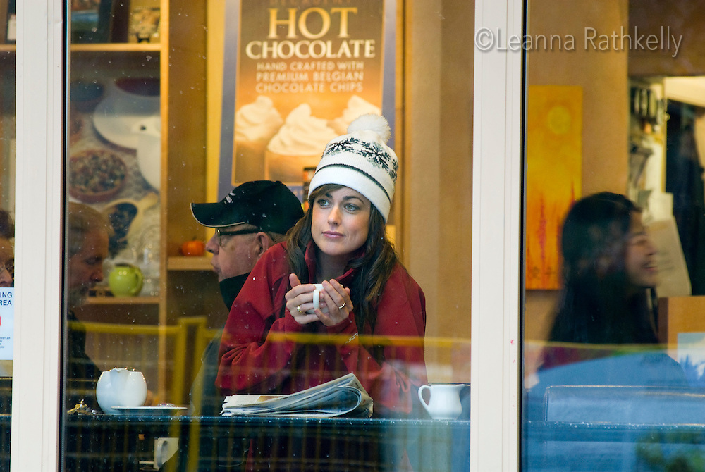 A woman enjoys a hot drink at a coffee shop on a rainy day