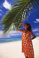 A nice asian girl under a palm tree leaf in Marshall Islands, Majuro Atoll