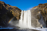 Tourists and rainbow at spectacular Skogar waterfall - Skogarfoss - in South Iceland with gushing glacial melting waters