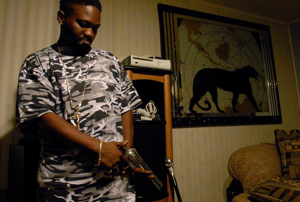 Big Rickie checks out a handgun during an all night party in Gary, Indiana. Members of the B-House deal in narcotics and prostitution. Big Rickie left the business to pursue a career in rap music and is owner and founder of Addicted Music.