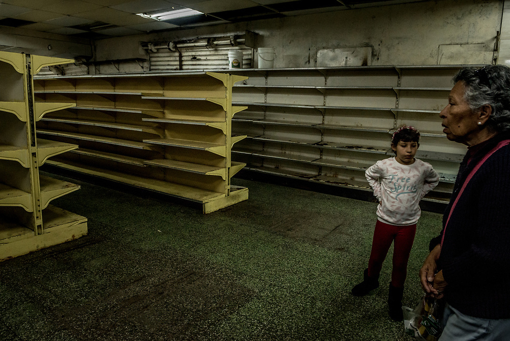 "GUAICAIPURO, VENEZUELA – MARCH 6, 2018: Shoppers search for food at a grocery store where nearly all shelves are empty because of massive food shortages plaguing the country amid an economic crisis. Declining nutrition and rising stress throughout the country have weakened immune systems, doctors and health-care specialists say, leaving a growing number of people more susceptible to illness like tuberculosis, malaria, diphtheria and measles. And with more people sinking into poverty, families have been forced to double-up in increasingly crowded homes, accelerating transmission. ""Tuberculosis is the shadow of misery,"" said Dr. José Félix Oletta, a former Venezuelan health minister. ""If there's a disease that is a marker of poverty, it's tuberculosis.""  PHOTO: Meridith Kohut for The New York Times"