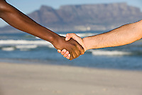 Multi-racial handshake Table MOuntain beach