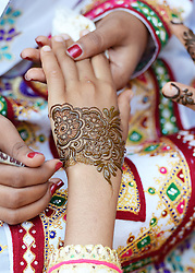 A young girl has a henna hand tattoo applied as The Prince of Wales visits the Ras Al Shajar nature reserve in south east Oman during his official tour of the Middle East.