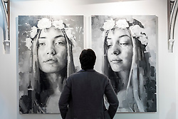 © Licensed to London News Pictures. 17/01/2017. London, UK. A man views paintings by Silvio Porzionato at the preview of the 29th London Art Fair, the UK's premier fair for Modern British and contemporary art, taking place at the Business Design Centre in Islington from 18-22 January 2017, where 129 galleries from 18 different countries will be presenting their artworks. Photo credit : Stephen Chung/LNP