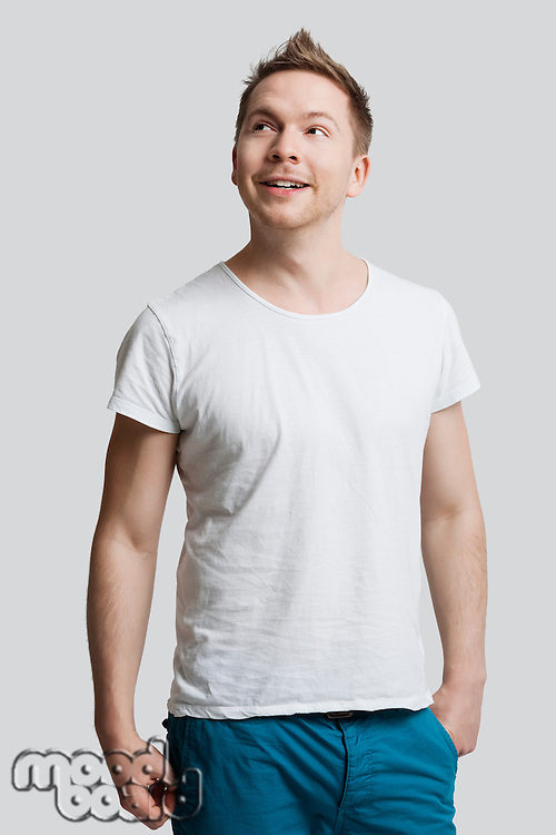 Young Caucasian man in casuals looking away against white background