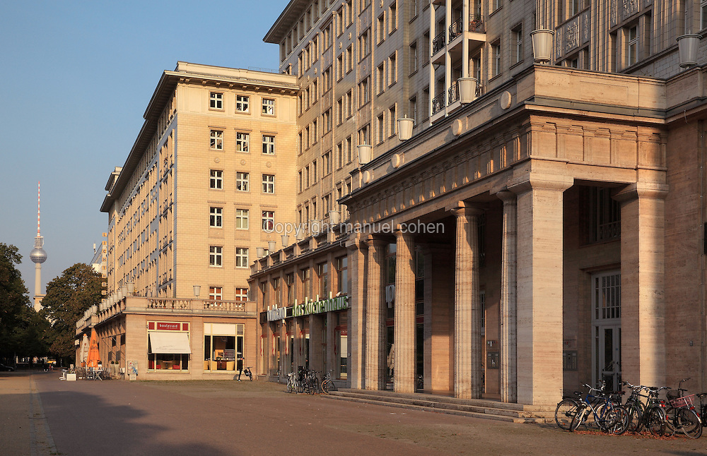 Buildings with shops and cafes on the ground floor on Karl Marx Allee, a monumental socialist boulevard built 1952-65 by the former East German state, with the Fernsehturm or Television Tower in the distance, Berlin, Germany. Picture by Manuel Cohen