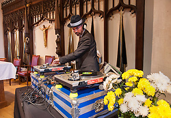 © Licensed to London News Pictures.22/04/2016. Bristol, UK.  A DJ in church for the funeral of DEREK SERPELL-MORRIS known as DJ DEREK at St Agnes Church, St Pauls, Bristol. Derek then aged 73 went missing on 10 July 2015 in Bristol. His remains were discovered by a member of the public by Filton airfield near Cribbs Causeway on 10 March 2016. A former accountant at Cadburys, Derek became a DJ playing 60s rocksteady, reggae, ska, dancehall and soul music and in his middle age became a well known and respected DJ of Black and Jamaican music in Bristol and further afield.  He played numerous gigs across the UK and appeared at many festivals including Glastonbury Festival. He also released his own compilation album, worked with Massive Attack and appeared in a Dizzee Rascal video. Photo credit : Simon Chapman/LNP