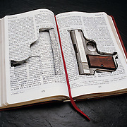 Pistol hidden in Bible with cut-out pages.