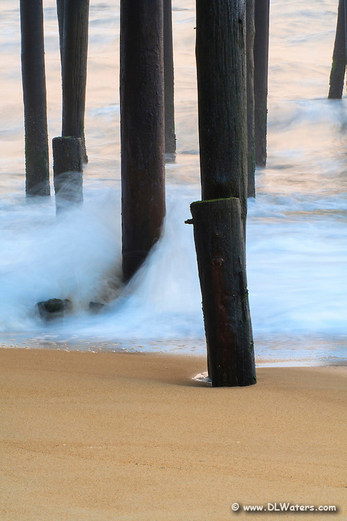 A long exposure creates soft waves at sunrise under Kitty Hawk Fishing Pier on the Outer Banks.