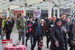 """St Pancras, London, January 16th 2016. Dozens of protesters hold an """"emergency demonstration and die-in"""" as France prepares to bulldoze the Jungle Camp at Calais. PICTURED: Protesters march from Kings Cross Square towards the main entrance of the Eurostar terminal at St Pancras.///FOR LICENCING CONTACT: paul@pauldaveycreative.co.uk TEL:+44 (0) 7966 016 296 or +44 (0) 20 8969 6875. ©2016 Paul R Davey. All rights reserved."""