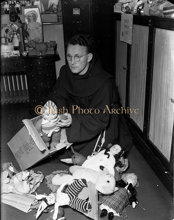 09/11/1952<br /> 11/09/1952<br /> 09 November 1952<br /> Rev. Fr. Lucius McClean, O.F.M. with toys preparing for the Franciscan toy competition, at Merchants Quay, Dublin.