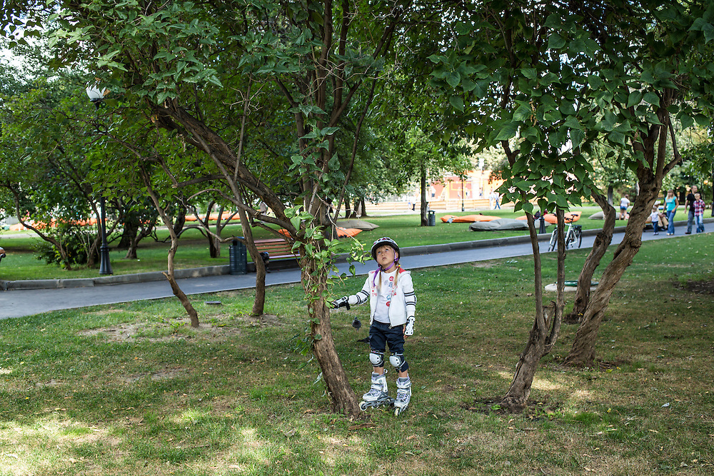 A girl looks at a squirrel in a tree in Gorky Park on Saturday, August 17, 2013 in Moscow, Russia.