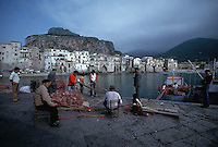 May 1979, Cefalu, Sicily, Italy --- Fishermen Repairing a Fishing Net --- Image by © Owen Franken/CORBIS