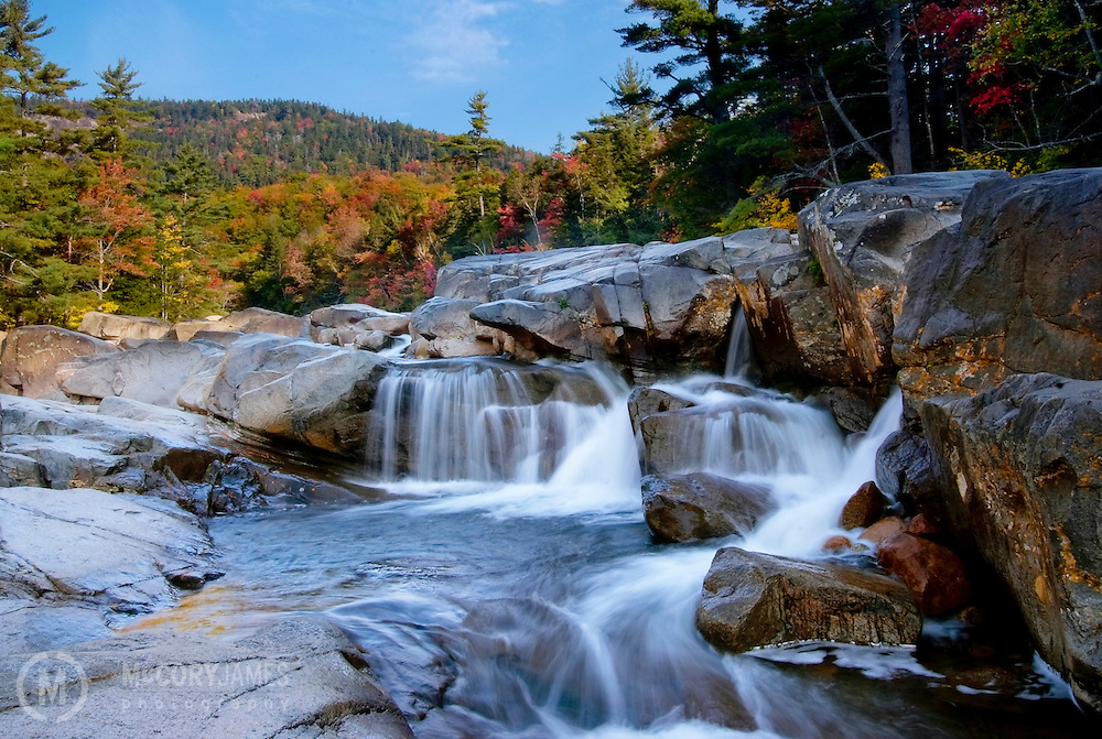 Waterfall with autumn colors in the background alongside the Kancamagus Scenic Byway in New Hampshire