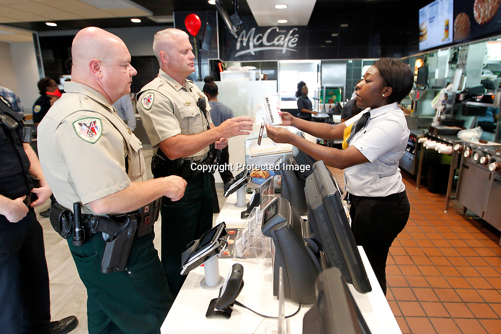 Sergeant Sam Riley and Corporal Mitchell Bridges, deputies with the Lee County Sheriff's Department, receive their cups from Chasity Dilworth, swing manager at McDonald's, during the restaurant's ribbon cutting ceremony at the Main Street location in Tupelo Monday morning.