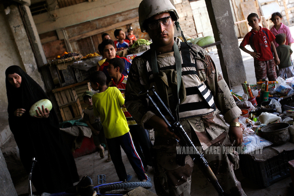 IRAQ, BASRA - JULY 5: An Iraqi soldier participates in a joint patrol with US Marines through a marketplace in the poverty stricken neighborhood of Hayaniyah, July 5, 2008 in Basra, Iraq. When British forces withdrew in 2007, Basra deteriorated into street battles between numerous Shiite militias and criminal gangs. In April 2008, Iraqi prime minister, Nouri al Maliki, sent two Iraqi army divisions to retake control of Basra. While the fighting has ended, unemployment is rife, at about 70 per cent. Since early 2008, Iraq's security situation has improved with oil production increasing, record government surplus and easing sectarian tensions. (Photo by Warrick Page)