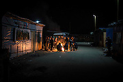 FRANCE, Calais: 18 January 2016 Refugees attempt to keep warm as blankets and shoes burn in a fire during subzero temperatures. <br /> Teamed with an astonishing sunrise and ice cold conditions, it resembled a post  apocalyptic scene. A scene that an estimated 7,000 people have to live in.<br /> Rick Findler / Story Picture Agency