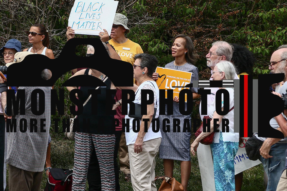 "Congressional Candidate Lisa Blunt Rochester, Center, holds a sign that reads ""Standing On The Side Of Love"" during a rededication ceremony Sunday, August 21, 2016, at First Unitarian Church in Wilmington."